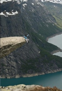 Sitting on the Trolltunga rock in Norway